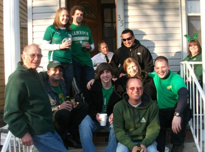 That's my Uncle Tommy, seated in the front on the right, with glasses and a green hoodie. We are on his front porch, celebrating our Irish heritage after watching the local parade, just like we did every year.